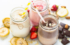 Set of milkshake in jars. Banana chocolate and strawberry milkshakes with nuts and coconut. Summer dessert. Healthy food on white.